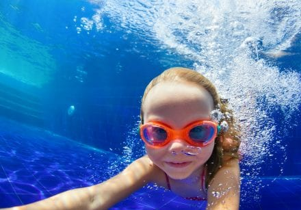 A girl with goggles swims at the bottom of a swimming pool