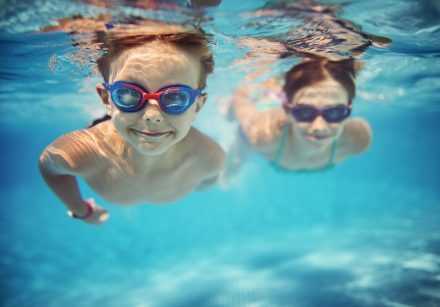 A girl and boy with goggles smile and swim underwater towards the camera