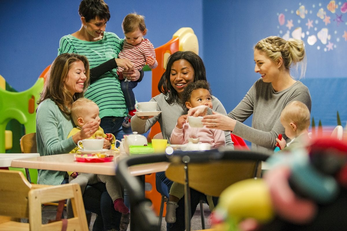 A group of mums and babies eat and drink in a play cafe