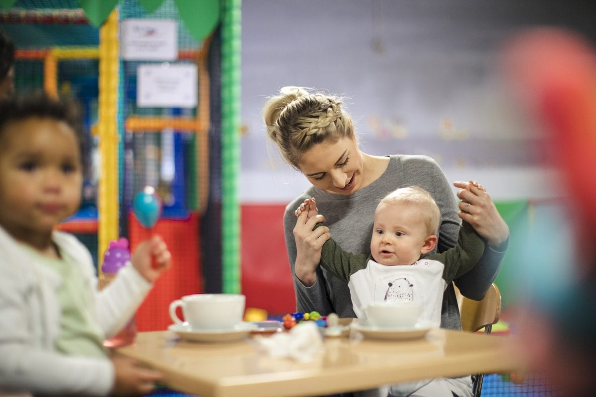 A mum sits at a table with her baby on her knee in a play cafe
