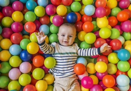 A baby plays in a ball pit filled with bright, colourful balls