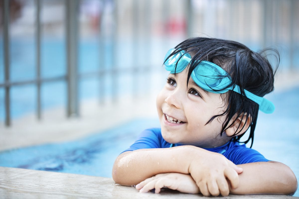 A young boy with goggles smiles up at his parent from the swimming pool