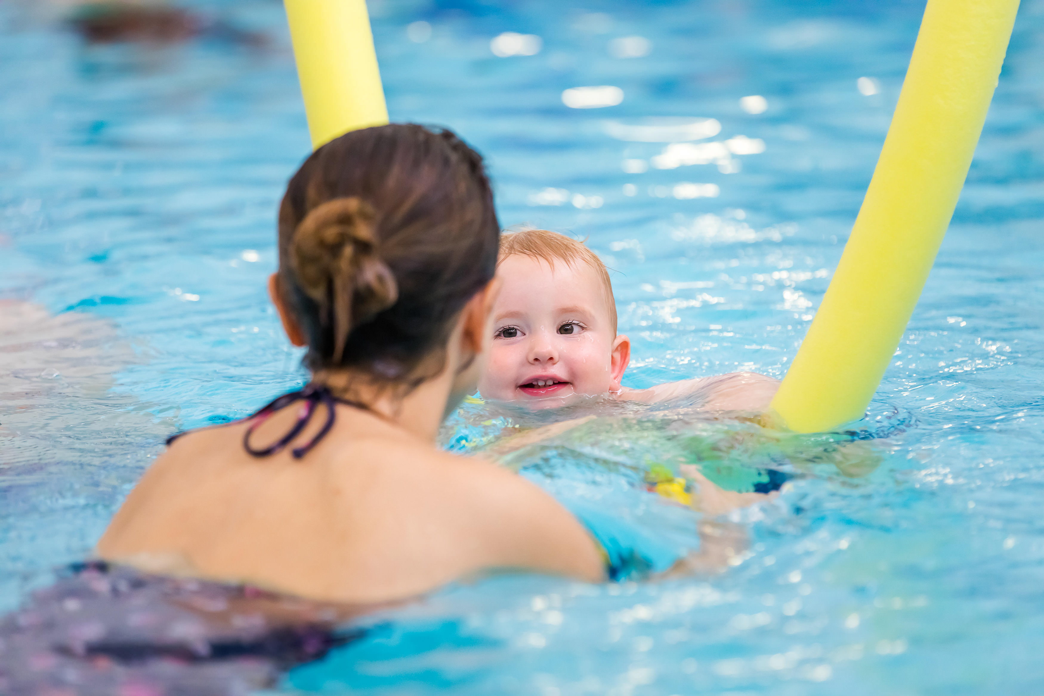 A young boy uses a yellow woggle to learn to swim with his mum