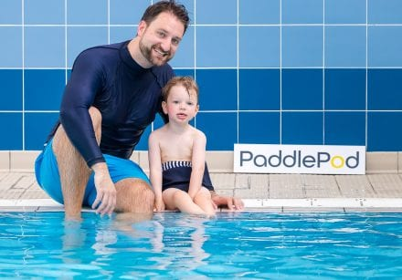 Phil Groom, founder of PaddlePod, sits on the side of the pool with his son