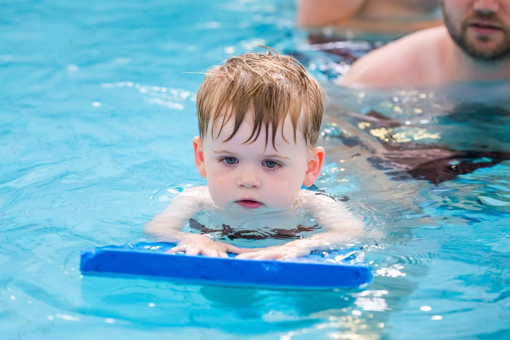 A young boy uses floatation aids to learn to swim independently