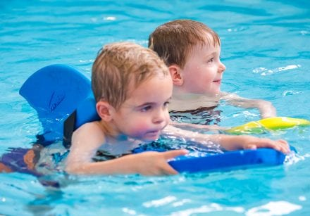 Two young boys swim using floatation aids during a pre-school swimming lesson