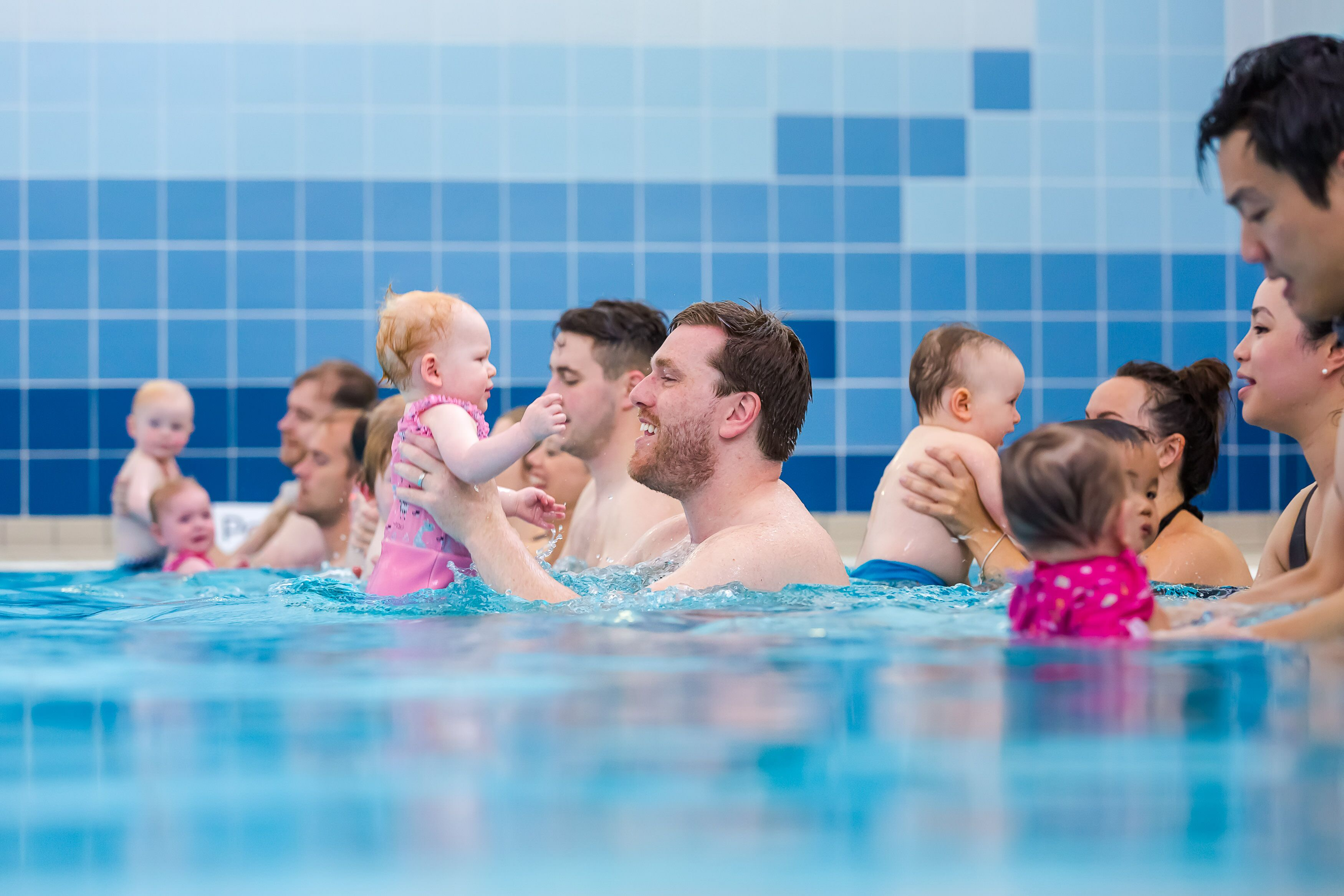 A dad and baby girl enjoy a baby swimming lesson