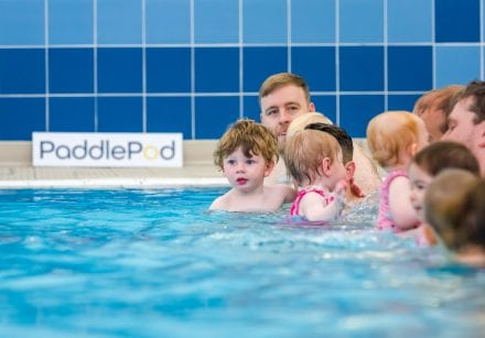 Group of parents and children enjoy a baby swimming lesson together